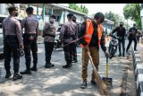Warga yang melanggar protokol kesehatan menyapu bahu jalan saat terjaring Operasi Yustisi Protokol COVID-19 di kawasan Jati Padang, Jakarta, Kamis (17/9/2020). Polda Metro Jaya dalam operasi gabungan tersebut hingga Selasa (15/9) mencatat telah memberikan sanksi terhadap 9.734 pelanggar PSBB Jakarta dengan nilai denda sebesar Rp88,6 juta. ANTARA FOTO/Aprillio Akbar/nym.