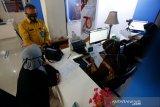 Kepala Kantor Imigrasi Kelas I TPI Banda Aceh Telmaizul Syatri berbincang dengan warga yang membuat paspor di Banda Aceh, Aceh, Kamis (17/9/2020). Sejak merebaknya pandemi COVID-19 jumlah permohonan pembuatan paspor menurun drastis dari 2.000 lebih pemohon menjadi kurang dari 100 pemohon setiap bulannya. Antara Aceh/Irwansyah Putra.