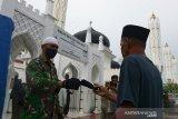 Personil TNI membagikan masker kepada jamaah yang hendak menunaikan Shalat Jumat di Masjid Raya Baiturrahman, Banda Aceh, Aceh, Jumat (18/9/2020). Pemerintah Aceh memperketat penerapan protokol kesehatan termasuk di masjid , rumah ibadah lainnya dan pusat keramaian dengan disertai sanksi sosial bagi pelanggar sehubungan terjadinya peningkatan kasus  COVID-19. Antara Aceh/Ampelsa.