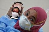 Seorang tenaga kesehatan Poli Pinere melakukan panggilan video dengan ibunya yang sedang dirawat karena positif COVID-19, di Rumah Sakit Umum Daerah (RSUD) Arifin Achmad, Kota Pekanbaru, Riau, Rabu (16/9/2020). Melonjaknya kasus COVID-19 membuat tenaga kesehatan mengalami kelelahan fisik dan mental karena selain menangani pasien juga harus memperhatikan keluarganya yang terpapar COVID-19. ANTARA FOTO/FB Anggoro/aww.