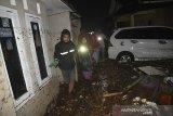 Warga melintasi genangan banjir bandang di Desa Mekarsari, Kecamatan Cicurug, Kabupaten Sukabumi, Jawa Barat, Senin (21/9/2020). Banjir bandang karena hujan deras tersebut mengakibatkan satu rumah warga terseret arus dan dua orang dilaporkan hilang terbawa arus. ANTARA JABAR/Iman Firmansyah/agr