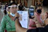 Petugas memotret penerima Bantuan Sosial Tunai (BST) tahap enam di kawasan Batubulan, Gianyar, Bali, Senin (21/9/2020). Kantor Pos Gianyar menyalurkan BST tahap enam senilai Rp300 ribu kepada 39.909 orang Keluarga Penerima Manfaat di empat wilayah kerja yaitu Kabupaten Gianyar, Klungkung, Bangli dan Karangasem untuk membantu meringankan beban ekonomi masyarakat yang terdampak pandemi COVID-19 dengan menerapkan protokol kesehatan yang ketat. ANTARA FOTO/Fikri Yusuf/nym.