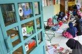 Anak-anak membaca buku dan bermain di Kampung Ramah Anak, Babakan Kalangsari, Kota Tasikmalaya, Jawa Barat, Selasa (22/9/2020). Kampung ramah anak yang menyediakan fasilitas permainan tradisional sekaligus taman bacaan itu bertujuan untuk mengajarkan anak bersosialisasi dan membudayakan gotong royong, agar anak-anak terhidar dari bahaya negatif perkembangan zaman khususnya teknologi. ANTARA JABAR/Adeng Bustomi/agr
