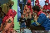 Kader posyandu Puspasari menimbang berat badan anak disaksikan Supervisor HSSE Ardi Hutri Prayitno (kanan) saat layanan penyuluhan posyandu jemput bola dengan aplikasi Sistem Infomasi Posyandu Terintegrasi (Sipter) di Tanjungsari, Kota Tasikmalaya, Jawa Barat, Rabu (23/9/2020). PT Pertamina (Persero) bekerja sama dengan Masyarakat Peduli Posyandu Indonesia membantu meningkatkan layanan Posyandu di Tasikmalaya melalui program Corporate Social Responsibility (CSR) dengan aplikasi Sipter untuk mempermudah dan membantu kader posyandu dalam penyuluhan, pencatatan data ibu hamil, bayi, balita serta pasangan usia subur. ANTARA JABAR/Adeng Bustomi/agr
