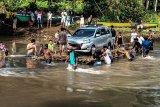 Suasana warga mendorong rakit di Kali Saweri, Kepulauan Yapen, Papua, Selasa (22/9/20). Terputusnya jembatan Kali Saweri yang menghubungkan Distrik Teluk Ampimoi dan Distrik Yapen Timur, warga Kampung Randawaya 2 (dua) di Distrik Ampimoi berinisiatif merakit bambu untuk menyeberangi kendaraan motor dan mobil. Apner Ambokari salah satu pengguna jalan mengaku sekali menyeberang, mobil dikenakan biaya Rp.100 ribu dan motor dikenakan biaya Rp.50 ribu. ANTARA FOTO/Paul Merani/ith/hp.