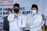 Pasangan calon Bupati dan wakil Bupati Banyuwangi Yusuf Widiyatmoko (kiri) dan H. Muhammad Riza Aziziy (kanan) menunjukan nomor urut 1 hasil pengundian oleh KPU di Banyuwangi, Jawa Timur, Kamis (24/9/2020). Hasil pengundian nomor urut Calon Bupati dan Wakil Bupati Banyuwangi, pasangan Yusuf Widiyatmoko dan H. Muhammad Riza Aziziy mendapatkan no urut 1 (satu), sedangkan  Ipuk Fiestiandani Azwar Anas dan H. Sugirah mendapatkan nomor urut 2 (dua). Antara Jatim/Budi Candra Setya/zk