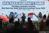 Maskot Pemilihan Wali Kota Surabaya Siro (kiri) dan Siboy (kanan) mengiringi penyanyi Cita Helmy (tengah) saat Deklarasi Kampanye Damai di Surabaya, Jawa Timur, Sabtu (26/9/2020). Deklarasi yang diselenggarakan oleh KPU Kota Surabaya tersebut mengharapkan agar kedua pasangan calon dan setiap elemen yang terlibat dalam proses kampanye Pilkada Surabaya 2020 menjadi pelopor dalam penerapan protokol kesehatan pencegahan COVID-19 dengan