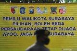 Polisi mengenakan masker saat berjaga di sekitar lokasi acara Deklarasi Kampanye Damai di Surabaya, Jawa Timur, Sabtu (26/9/2020). Deklarasi yang diselenggarakan oleh KPU Kota Surabaya tersebut mengharapkan agar kedua pasangan calon dan setiap elemen yang terlibat dalam proses kampanye Pilkada Surabaya 2020 menjadi pelopor dalam penerapan protokol kesehatan pencegahan COVID-19 dengan