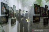 Pengunjung melihat karya seni lukisan saat Pameran Satu Ruang Dua Pintu di Ruang Dini, Bandung, Jawa Barat, Minggu (27/9/2020). Pameran seni kolaborasi karya Sandy Tisa dan Erik Rifky tersebut melukiskan tentang sebuah ruang dialog hiruk pikuk persoalan kehidupan dan pertumbuhan peradaban yang mempengaruhi kehidupan rural yang berubah menjadi suburban melalui industri. ANTARA JABAR/Novrian Arbi/agr