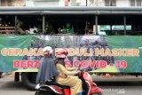 Anggota Bekangdam bersama ibu Persit Kodam Iskandar Muda menjahit masker kain dalam mobil truk saat parkir di kawasan Masjid Raya Baiturrahman, Banda Aceh, Aceh, Selasa (29/9/2020). Aksi membawa mesin jahit untuk memproduksi masker kain yang dibagikan secara gratis kepada warga kota itu, salah satu upaya mengkampanyekan Gerakan Peduli Masker dalam mencegah penyebaran COVID-19. Antara Aceh/Ampelsa.