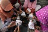 Sejumlah anak membatik masker kain di Kelurahan Dermo, Kota Kediri, Jawa Timur, Jumat (2/10/2020). Membatik dengan media masker yang diselenggarakan pemerintah daerah setempat tersebut guna memperingati Hari Batik Nasional sekaligus sosialisasi penerapan protokol kesehatan saat pandemi COVID-19 kepada anak-anak. Antara Jatim/Prasetia Fauzani/zk.
