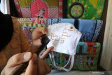 Seorang anak membatik masker kain di Kelurahan Dermo, Kota Kediri, Jawa Timur, Jumat (2/10/2020). Membatik dengan media masker yang diselenggarakan pemerintah daerah setempat tersebut guna memperingati Hari Batik Nasional sekaligus sosialisasi penerapan protokol kesehatan saat pandemi COVID-19 kepada anak-anak. Antara Jatim/Prasetia Fauzani/zk.