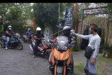 Petugas memeriksa suhu tubuh peserta 'touring' sepeda motor bertajuk