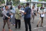 Polisi melayani warga yang antre untuk menjemput keluarganya yang diamankan di Polrestabes Surabaya, Jawa Timur, Jumat (9/10/2020). Polrestabes Surabaya mengembalikan 231 anak kepada keluarganya dari 253 orang yang ditangkap saat unjuk rasa buruh Tolak UU Cipta Kerja pada Kamis (8/10/2020), sedangkan 22 orang sisanya ditetapkan menjadi tersangka atas kasus dugaan perusakaan fasilitas umum. Antara Jatim/Didik/Zk