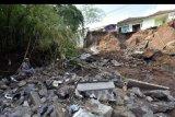 Warga melihat kondisi jalan yang putus akibat cuaca ekstrem yang terjadi di Lingkungan Sanggulan, Desa Banjar Anyar, Tabanan, Minggu (11/10/2020). Badan Penanggulangan Bencana Daerah (BPBD) Kabupaten Tabanan mendata ada 58 titik kejadian bencana akibat hujan deras yang mengguyur wilayah itu pada Sabtu (10/10/2020) dengan total kerugian mencapai sekitar miliaran rupiah, korban terluka satu orang dan nihil korban jiwa. ANTARA FOTO/Nyoman Hendra Wibowo/nym.