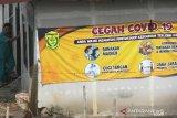 Warga melintas di dekat spanduk himbauan protokol kesehatan COVID-19 di Kawasan Banua Anyar, Banjarmasin, Kalimantan Selatan, Senin (12/10/2020). Pemerintah terus berupaya menekan penyeberan virus corona dengan mengampanyekan perilaku hidup disiplin salah satu cara selalu melakukan langkah Memakai masker, Mencuci Tangan, Menjaga Jarak dan Menghindari kerumunan (3M) sebagai upaya mencegah sekaligus memutus mata rantai penularan COVID-19. Foto Antaranews Kalsel/Bayu Pratama S.