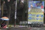 Penjual kembang menunggu pembeli di dekat spanduk himbauan protokol kesehatan COVID-19 di kawasan Pasar Sudimampir, Banjarmasin, Kalimantan Selatan, Senin (12/10/2020). Pemerintah terus berupaya menekan penyeberan virus corona dengan mengampanyekan perilaku hidup disiplin salah satu cara selalu melakukan langkah Memakai masker, Mencuci Tangan, Menjaga Jarak dan Menghindari kerumunan (3M) sebagai upaya mencegah sekaligus memutus mata rantai penularan COVID-19. Foto Antaranews Kalsel/Bayu Pratama S.