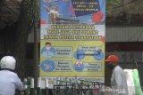 Warga melintas di dekat spanduk himbauan protokol kesehatan COVID-19 di kawasan Pasar Sudimampir, Banjarmasin, Kalimantan Selatan, Senin (12/10/2020). Pemerintah terus berupaya menekan penyeberan virus corona dengan mengampanyekan perilaku hidup disiplin salah satu cara selalu melakukan langkah Memakai masker, Mencuci Tangan, Menjaga Jarak dan Menghindari kerumunan (3M) sebagai upaya mencegah sekaligus memutus mata rantai penularan COVID-19. Foto Antaranews Kalsel/Bayu Pratama S.