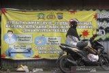 Warga bersantai di dekat spanduk himbauan protokol kesehatan COVID-19 di kawasan Pasar Sudimampir, Banjarmasin, Kalimantan Selatan, Senin (12/10/2020). Pemerintah terus berupaya menekan penyeberan virus corona dengan mengampanyekan perilaku hidup disiplin salah satu cara selalu melakukan langkah Memakai masker, Mencuci Tangan, Menjaga Jarak dan Menghindari kerumunan (3M) sebagai upaya mencegah sekaligus memutus mata rantai penularan COVID-19. Foto Antaranews Kalsel/Bayu Pratama S.
