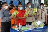 Kepala Badan Narkotika Nasional (BNN) Provinsi Aceh, Heru Pranoto (kedua kiri) bersama anggotanya memperlihatkan sejumlah barang bukti tindak kejahatan narkotika jenis sabu yang dikemas dalam bungkus teh China dan sejumlah ekstasi saat gelar perkara di Banda Aceh, Aceh, Selasa (13/10/2020). BNN Aceh menggagalkan peredaran sabu sebanyak sekitar delapan kilogram dan ekstasi 9.891 butir yang merupakan jaringan internasional dan mengamankan dua tersangka, sedangkan seorang tersangka lainnya buronan. Antara Aceh /Ampelsa.