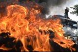 Sejumlah mahasiswa Universitas Islam Negeri (UIN) Makassar membakar ban bekas saat berunjuk rasa, di depan kampus UIN Alauddin, Makassar, Sulawesi Selatan, Selasa (6/10/2020). Dalam aksi unjuk rasa tersebut mereka menolak Undang-undang (UU) Omnibus Law Cipta Kerja yang telah disahkan oleh DPR pada Senin (5/10/2020) karena dinilai merugikan para pekerja dan hanya menguntungkan bagi pengusaha. ANTARA FOTO/Abriawan Abhe/hp.