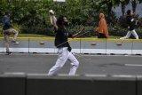 Seorang wanita berlari saat terjadi bentrokan antara petugas kepolisian dengan massa aksi tolak UU Cipta Kerja di kawasan jalan MH Thamrin, Jakarta, Selasa (13/10/2020). ANTARA FOTO/Muhammad Adimaja/nz.