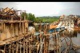 Warga berada di dekat lokasi proyek pembangunan jembatan jerambah gantung yang ambruk, di Pangkalpinang, Kepulauan Bangka Belitung, Sabtu (17/10/2020). Jembatan alternatif penghubung Kota Pangkalpinang dan Kabupaten Bangka, Kepulauan Bangka Belitung senilai Rp2.5 miliar tersebut ambruk pada Jumat (16/10/2020) malam. ANTARA FOTO/Anindira Kintara/nym