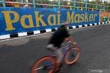 Pesepeda melintas di dekat dinding bermural di Surabaya, Jawa Timur, Minggu (18/10/2020). Mural di sepanjang dinding viaduk Gubeng itu sebagai sarana imbauan kepada masyarakat untuk menerapkan protokol kesehatan pencegahan penularan COVID-19. Antara Jatim/Didik/Zk