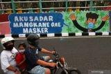 Pengendara motor melintas di dekat dinding bermural di Surabaya, Jawa Timur, Minggu (18/10/2020). Mural di sepanjang dinding viaduk Gubeng itu sebagai sarana imbauan kepada masyarakat untuk menerapkan protokol kesehatan pencegahan penularan COVID-19. Antara Jatim/Didik/Zk