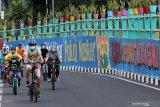 Sejumlah pesepeda melintas di dekat dinding bermural di Surabaya, Jawa Timur, Minggu (18/10/2020). Mural di sepanjang dinding viaduk Gubeng itu sebagai sarana imbauan kepada masyarakat untuk menerapkan protokol kesehatan pencegahan penularan COVID-19. Antara Jatim/Didik/Zk
