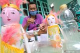 Perajin melakukan proses pewarnaan saat pembuatan boneka di Desa Turus, Kediri, Jawa Timur, Senin (19/10/2020). Boneka berbahan baku botol minuman bekas yang dapat difungsikan sebagai tempat penyimpanan uang tersebut dijual seharga Rp20.000-Rp30.000 per pesang tegantung tingkat kerumitan pembuatan. Antara Jatim/Prasetia Fauzani/zk