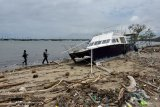 Pemancing melintas di dekat sampah kiriman yang berserakan di Pantai Muntig Siokan, Desa Sanur Kauh, Denpasar, Bali, Selasa (20/10/2020). Sampah kiriman berupa potongan kayu, potongan bambu dan plastik yang berserakan di sepanjang pantai tersebut diakibatkan terbawa arus gelombang laut karena cuaca ekstrem yang melanda Bali akhir-akhir ini. ANTARA FOTO/Nyoman Hendra Wibowo/nym.