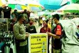 Personel Polsek Pahandut ingatkan pengunjung dan pedagang Pasar Besar terapkan 3M
