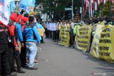 Polisi berjaga dengan membawa poster imbauan saat sejumlah buruh berunjuk rasa di depan gedung DPRD Jawa Timur, Surabaya, Jawa Timur, Kamis (22/10/2020). Massa buruh menyerukan 'Tolak dan Batalkan Undang-Undang Cipta Kerja'. Antara Jatim/Didik/Zk
