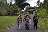 Sejumlah warga yang tubuhnya dihias warna-warni dan menggunakan masker saat berkeliling kampung dalam tradisi Ngerebeg di Desa Tegallalang, Gianyar, Bali, Kamis (22/10/2020). Tradisi yang merupakan ritual tolak bala tersebut biasanya diikuti ratusan warga, namun tahun ini digelar dengan jumlah terbatas sekitar 36 orang dengan menerapkan protokol kesehatan COVID-19. ANTARA FOTO/Nyoman Hendra Wibowo/nym.