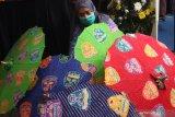 Perajin menata produk payung batik karyanya dalam Festival Batik di Gedung Kartini, Malang, Jawa Timur, Jumat (23/10/2020). Kegiatan untuk mengenalkan berbagai macam produk batik kepada masyarakat tersebut diadakan selama tujuh hari dengan menerapkan pembayaran secara digital yaitu melalui kode quick response (QR). Antara Jatim/Ari Bowo Sucipto/zk