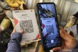 Pengunjung melakukan pembayaran secara digital  dengan memindai kode quick respons (QR) saat membeli sepatu batik decal dalam Festival Batik di Gedung Kartini, Malang, Jawa Timur, Jumat (23/10/2020). Kegiatan untuk mengenalkan berbagai macam produk batik kepada masyarakat tersebut diadakan selama tujuh hari dengan menerapkan pembayaran secara digital yaitu melalui kode quick response (QR). Antara Jatim/Ari Bowo Sucipto/zk