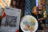 Perajin menata produk piring decal batik karyanya dalam Festival Batik di Gedung Kartini, Malang, Jawa Timur, Jumat (23/10/2020). Kegiatan untuk mengenalkan berbagai macam produk batik kepada masyarakat tersebut diadakan selama tujuh hari dengan menerapkan pembayaran secara digital yaitu melalui kode quick response (QR). Antara Jatim/Ari Bowo Sucipto/zk