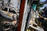 Seorang jurnalis mengambil gambar kondisi rumah yang terbakar di Legok, Kabupaten Tangerang, Banten, Jumat (23/10/2020). Kebakaran yang terjadi pada Jumat (23/10/2020) dini hari tersebut diduga akibat korsleting listrik dan menyebabkan lima anggota keluarga di rumah tersebut meninggal dunia. ANTARA FOTO/Fauzan/nym.