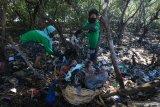 Warga memunguti sampah plastik yang berserakan di pesisir Tambak Wedi, Surabaya, Jawa Timur, Minggu (25/10/2020). Kegiatan yang dilakukan  oleh Tunas Hijau bersama sejumlah pelajar, guru dan keluarganya itu wujud kepedulian terhadap kebersihan lingkungan di kawasan pantai. Antara Jatim/Didik/Zk