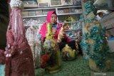 Perajin merekatkan pita pada botol untuk digunakan sebagai hiasan di Kota Kediri, Jawa Timur, Minggu (25/10/2020). Hiasan dari botol bekas yang dipadukan dengan pita dan rajut tersebut dijual secara daring seharga Rp40 ribu hingga Rp80 ribu per botol. Antara Jatim/Prasetia Fauzani/zk