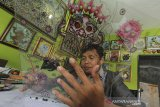Kusdono Rastika (39) menyelesaikan kerajinan lukis kaca di Desa Gegesik Lor, Gegesik, Kabupaten Cirebon, Jawa Barat, Minggu (25/10/2020). Seni lukis kaca khas Cirebon itu dijual seharga Rp300 ribu hingga Rp10 juta tergantung ukuran dan tingkat kerumitan. ANTARA JABAR/Dedhez Anggara/agr