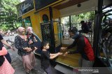 Petugas memberikan cairan antiseptik kepada wisatawan sebelum menaiki bus untuk keliling kota di Kawasan Tugu 0 Km, Banjarmasin, Kalimantan Selatan, Minggu (25/10/2020). Pemprov Kalsel bekerja sama dengan tiga asosiasi pariwisata mengoperasikan dua unit bus wisata yang diberi nama Bus Bejalanan dengan menawarkan rekreasi berkeliling Kota Banjarmasin. Hal tersebut untuk menggaet wisatawan serta membangkitkan perekonomian sektor wisata yang terpuruk akibat pandemi COVID-19. Foto Antaranews Kalsel/Bayu Pratama S.