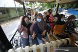 Wisatawan menaiki bus untuk berkeliling kota di Kawasan Tugu 0 Km, Banjarmasin, Kalimantan Selatan, Minggu (25/10/2020). Pemprov Kalsel bekerja sama dengan tiga asosiasi pariwisata mengoperasikan dua unit bus wisata yang diberi nama Bus Bejalanan dengan menawarkan rekreasi berkeliling Kota Banjarmasin. Hal tersebut untuk menggaet wisatawan serta membangkitkan perekonomian sektor wisata yang terpuruk akibat pandemi COVID-19. Foto Antaranews Kalsel/Bayu Pratama S.