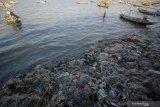 Warga kampung nelayan Nambangan beraktivitas di pinggir pantai Kenjeran yang dipenuhi sampah di Surabaya, Jawa Timur, Sabtu (24/10/2020). Menurut warga setempat, sampah-sampah tersebut selain dibawa arus hingga ke pantai juga berasal dari kebiasaan buruk masyarakat di kampung nelayan itu yang membuang sampah sembarangan. Antara Jatim/Moch Asim/zk.
