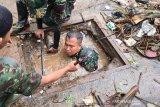 Anggota TNI menyelami parit untuk membersihkan sampah di Sumedang