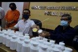 Petugas menunjukkan tersangka berinisial AMF (kiri) dan barang bukti produk obat ilegal saat rilis di Polda Bali, Denpasar, Bali, Senin (26/10/2020). Petugas Balai Besar Pengawas Obat dan Makanan (BBPOM) Denpasar bersama Ditreskrimsus Polda Bali berhasil mengamankan barang bukti sediaan farmasi yang tidak memenuhi syarat dan tanpa izin edar berupa 31.179 tablet obat yang mengandung Tiheksifenidil dan 5.172 tablet obat dengan kandungan Dextromethorpan yang akan diedarkan tersangka AMF. ANTARA FOTO/Fikri Yusuf/nym