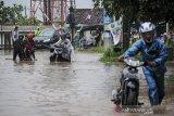 Warga mendorong motornya yang mogok akibat banjir di Jalan Cibiru Hilir, Kabupaten Bandung, Jawa Barat, Selasa (27/10/2020). Hujan yang mengguyur Bandung Raya sejak siang hingga sore hari membuat jalanan tersebut tergenang air setinggi 10 hingga 50 sentimeter akibat luapan sungai. ANTARA JABAR/Raisan Al Farisi/agr