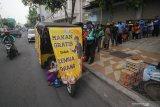 Warga mengantre untuk mendapatkan makanan secara gratis di gerobak makanan milik Setiyono di jalan Kedungsari, Surabaya, Jawa Timur, Selasa (27/10/2020). Aksi sosial pemberian makan gratis untuk semua orang sebanyak 100 porsi setiap hari tersebut guna membantu meringankan beban ekonomi masyarakat di tengah pandemi COVID-19. Antara Jatim/Moch Asim/zk.
