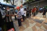 Setiyono (kiri) membagikan makan gratis kepada warga yang mengantre di jalan Kedungsari, Surabaya, Jawa Timur, Selasa (27/10/2020). Aksi sosial pemberian makan gratis untuk semua orang sebanyak 100 porsi setiap hari tersebut guna membantu meringankan beban ekonomi masyarakat di tengah pandemi COVID-19. Antara Jatim/Moch Asim/zk.